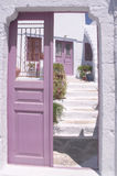 Greek welcome. The open door is a traditional Greek way of indicating that visitors are welcome. The pink colour scheme on this house in Pyrgos, Santorini, is Stock Images