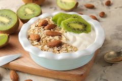 Greek white yoghurt with kiwi almonds and oatmeal on a light concrete table. breakfast. healthy food royalty free stock photos