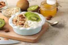 Greek white yoghurt with kiwi almonds and oatmeal on a light concrete table. breakfast. healthy food. Greek white yoghurt with kiwi almonds and oatmeal on a stock photos
