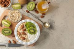 Greek white yoghurt with kiwi almonds and oatmeal on a light concrete table. breakfast. top view. healthy food stock image