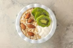 Greek white yoghurt with kiwi almonds and oatmeal on a light concrete table. breakfast. top view. healthy food royalty free stock images