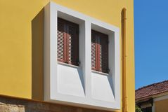 Greek window with wooden shutters. Brown wooden shutters with jalousie on the facade of a house in the old Greek city Stock Images