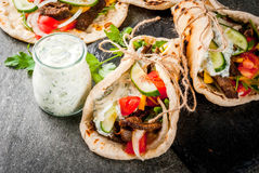 Greek wrapped sandwich gyros. Healthy snack, lunch. Traditional Greek wrapped sandwich gyros - tortillas, bread pita with a filling of vegetables, beef meat and Stock Image