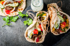 Greek wrapped sandwich gyros. Healthy snack, lunch. Traditional Greek wrapped sandwich gyros - tortillas, bread pita with a filling of vegetables, beef meat and Stock Photo
