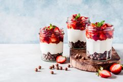 Yoghurt with Strawberries and Cereal. Greek Yoghurt with Strawberries, Honey  and Cereal in Jars, copy space for your text royalty free stock photo