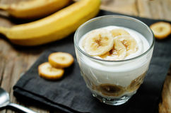 Greek yogurt banana parfait. On a wood background. toning. selective focus stock photography