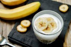 Greek yogurt banana parfaits. On a wood background. toning. selective focus stock photography