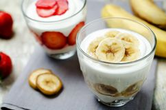 Greek yogurt banana parfaits. On a wood background. toning. selective focus royalty free stock photo