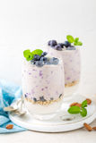 Greek yogurt or blueberry parfait with fresh berries and almond nuts on white background Stock Images
