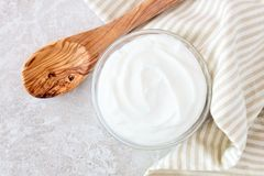 Greek yogurt, with cloth and spoon on white marble. Greek yogurt in a bowl, downward view with cloth and spoon on a white marble Stock Photography