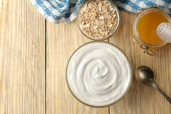 Greek yogurt in a glass bowl next to oatmeal and honey on a natural wood background. healthy food. natural yoghurt. breakfast. . t stock photos