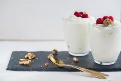 Greek yogurt in glass decorated with ripe raspberries, granola and nuts. Space for text. Breakfast concept. Healthy food Stock Photography