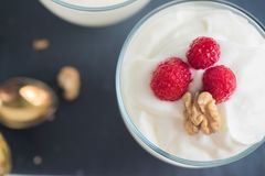 Greek yogurt in glass decorated with ripe raspberries, granola and nuts. Space for text. Breakfast concept. Healthy food Royalty Free Stock Image