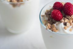 Greek yogurt in glass decorated with ripe raspberries, granola and nuts. Space for text. Breakfast concept. Healthy food Royalty Free Stock Images