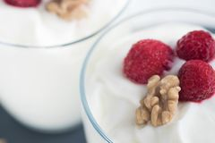 Greek yogurt in glass decorated with ripe raspberries, granola and nuts. Space for text. Breakfast concept. Healthy food Royalty Free Stock Photography