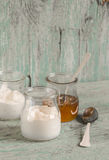 Greek yogurt and honey in a glass jar on blue wooden surface Royalty Free Stock Images