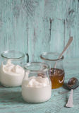 Greek yogurt and honey in a glass jar on blue wooden surface Stock Photography