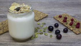Greek yogurt, milk, smoothies, blueberries and currants in a glass jar on a wooden table, detox, diet stock photo