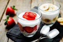 Greek yogurt strawberry and banana parfaits. On a wood background. toning. selective focus royalty free stock photography