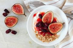 Greek yogurt with sweet figs, berries and granola, over marble Stock Photos