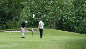 On the green. Two golfers at the flag Royalty Free Stock Photos