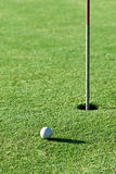 Green. A golf ball a short putt away from the hole with the flag still in it Stock Images