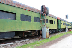 Green abandoned passenger train cars with boarded windows beside light posts on train tracks. Horizontal aspect Stock Photography