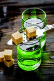 Absinthe shots with sugar cubes on wooden table background Stock Images