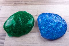 Green adn blue slime on a wooeden table.  stock image