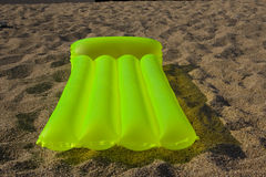 Green airbed lying on a sand. On a beach in Costa Brava - Spain Stock Photos