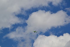 Green airplane. A colorful green airplane in flight at daytime Stock Photos