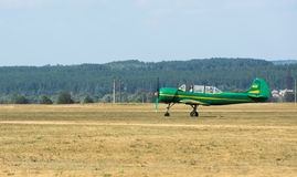 Green airplane with propeller on airfield Stock Photos