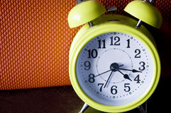 Green alarm clock. Green color alarm clock with orange color background Royalty Free Stock Image