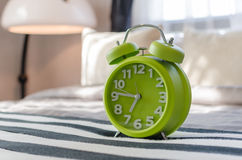 Green alarm clock on bed Royalty Free Stock Photos