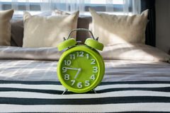 Green alarm clock on bed Stock Image