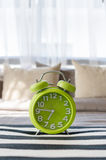 Green alarm clock in bedroom Stock Photo