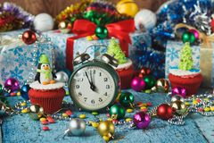 Green alarm clock and Christmas cupcakes with decorations made from confectionery mastic. Soft focus background Stock Photos