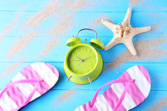 Alarm clock with flip flops. Green alarm clock with flip flops and starfish on blue wooden table stock photography