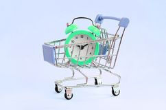 Green alarm clock in supermarket trolley on blue background stock image