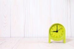 Green alarm clock on wood background Royalty Free Stock Image
