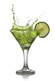 Green alcohol cocktail with splash and green lime royalty free stock photography