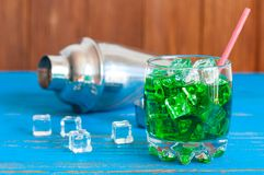 Green alcohol cocktail with straw, ice cubes and Royalty Free Stock Image