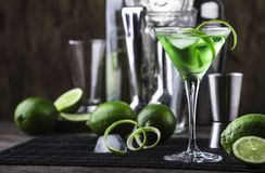Free Green Alcoholic Cocktail Martini Glass With Dry Gin, Vermouth, Liquor, Lime Zest And Ice, Bar Tools, Dark Background Stock Images - 166157384