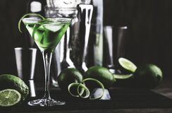 Free Green Alcoholic Cocktail Martini Glass With Dry Gin, Vermouth, Liquor, Lime Zest And Ice, Bar Tools, Dark Background Stock Photos - 179077923