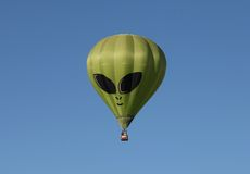 Green Alien Hot Air Balloon Against a Blue Sky Stock Image