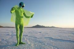 Green Alien Traveler Reading Map on Flexible Display Tablet Stock Images