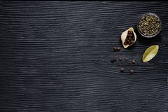 Green and allspice pepper, bay leaf on black rustic table, space for text. Big conchiglie with green pepper, bay leaf and allspice on rustic black wooden table stock photos