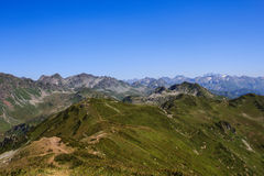 Green alpine meadows with sandy trails in caucasus mountains Stock Photo