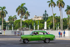 Green american vintage car drives on the main street in Havana City Royalty Free Stock Photography