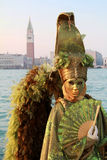 Green angel mask with feathered wings. San Marco tower in background . Venice Carnival 2012 Stock Image